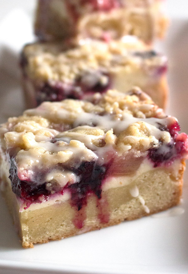 Blackberry Rhubarb Dream Bars with cheesecake filling and crumble top drizzled with icing for good measure. Perfect for a picnic, fancy brunch, or family breakfast. Just try to not eat the whole pan!